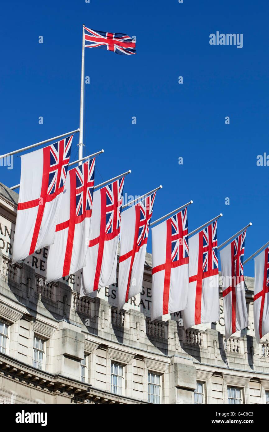 Royal Navy White Ensigns und Union Jack fliegen über Admiralty Arch entlang der Mall in London Stockbild