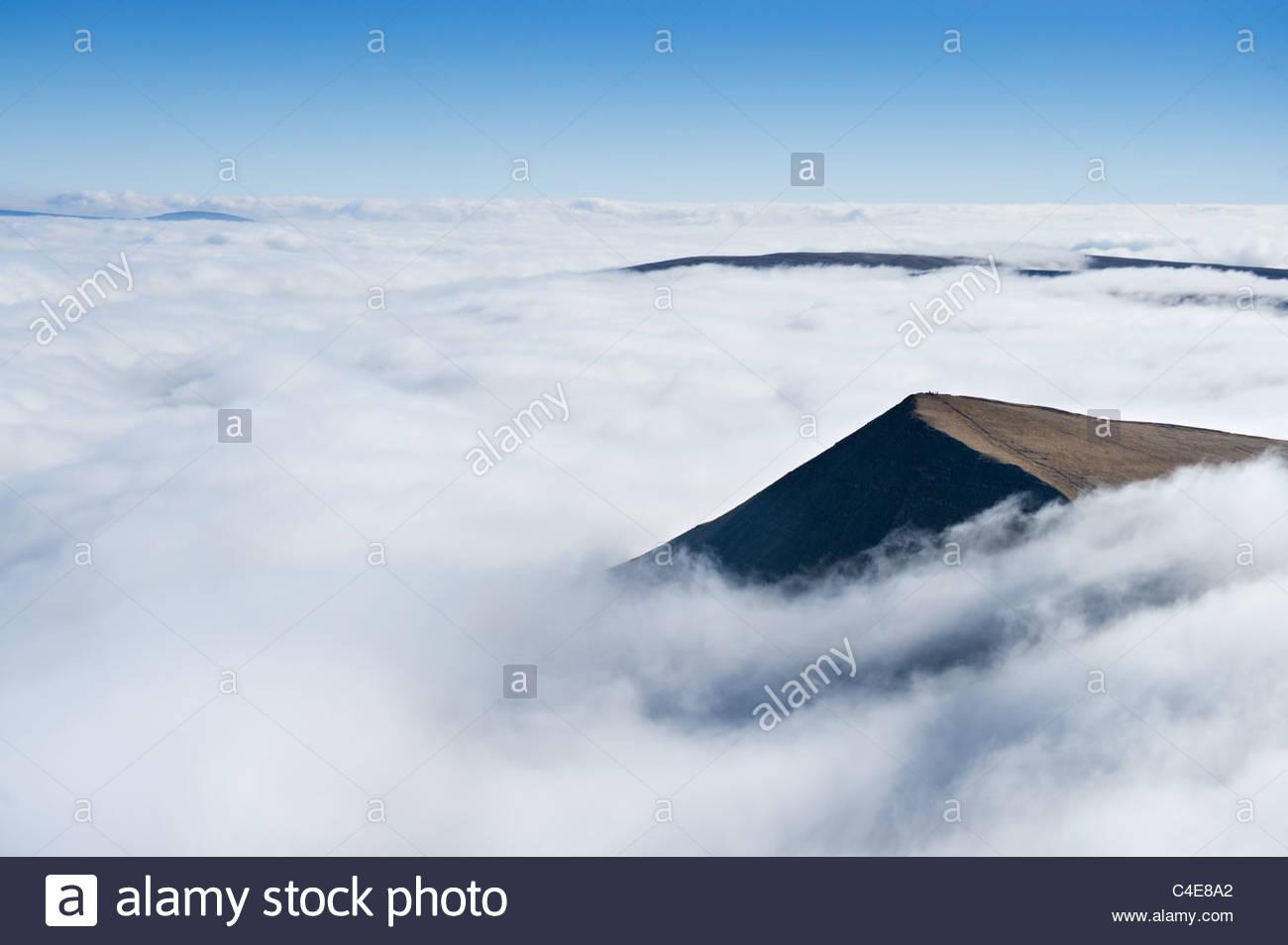 Wanderer auf dem Gipfel des Cribyn, erhebt sich über einem Meer von Cloud. Brecon Beacons National Park, Powys, Stockbild