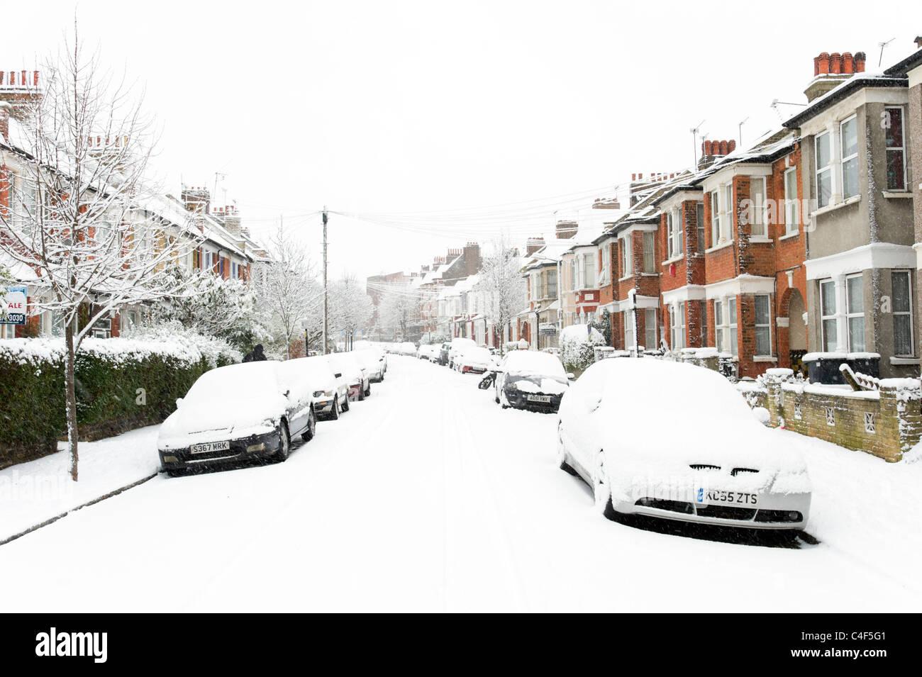 Verschneite Autos in Wohnstraße, London, UK Stockbild