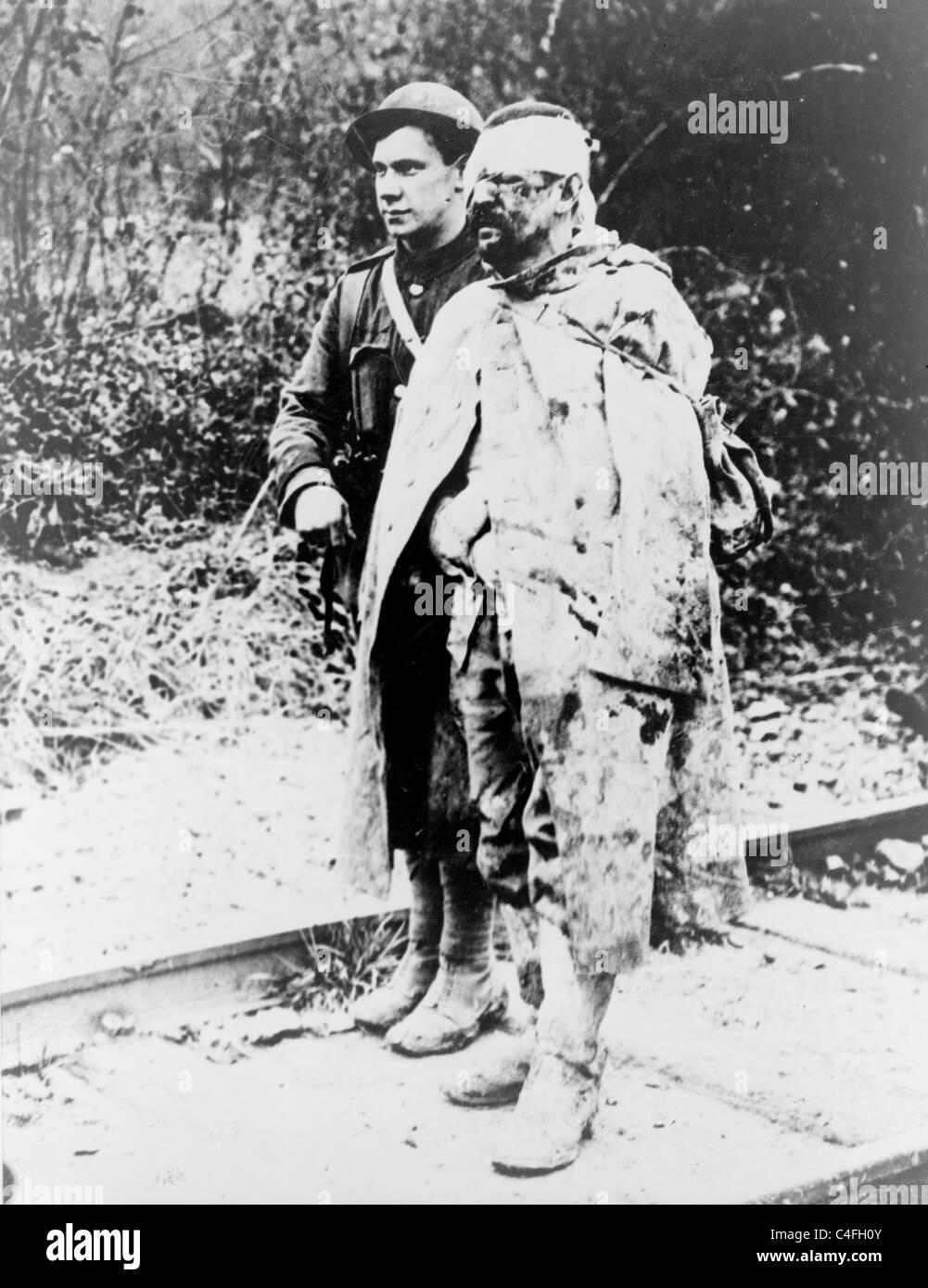 Eine britische Rote Kreuz geordnete eskortieren einen verwundeten, gefangen genommen, deutschen Soldat in einem Stockbild