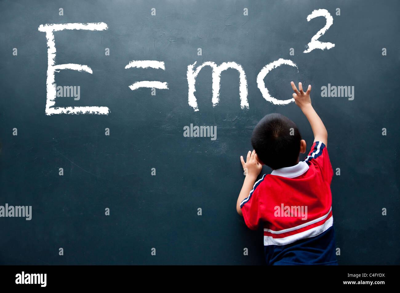 junge Zeichnung E = mc2 an der WandStockfoto