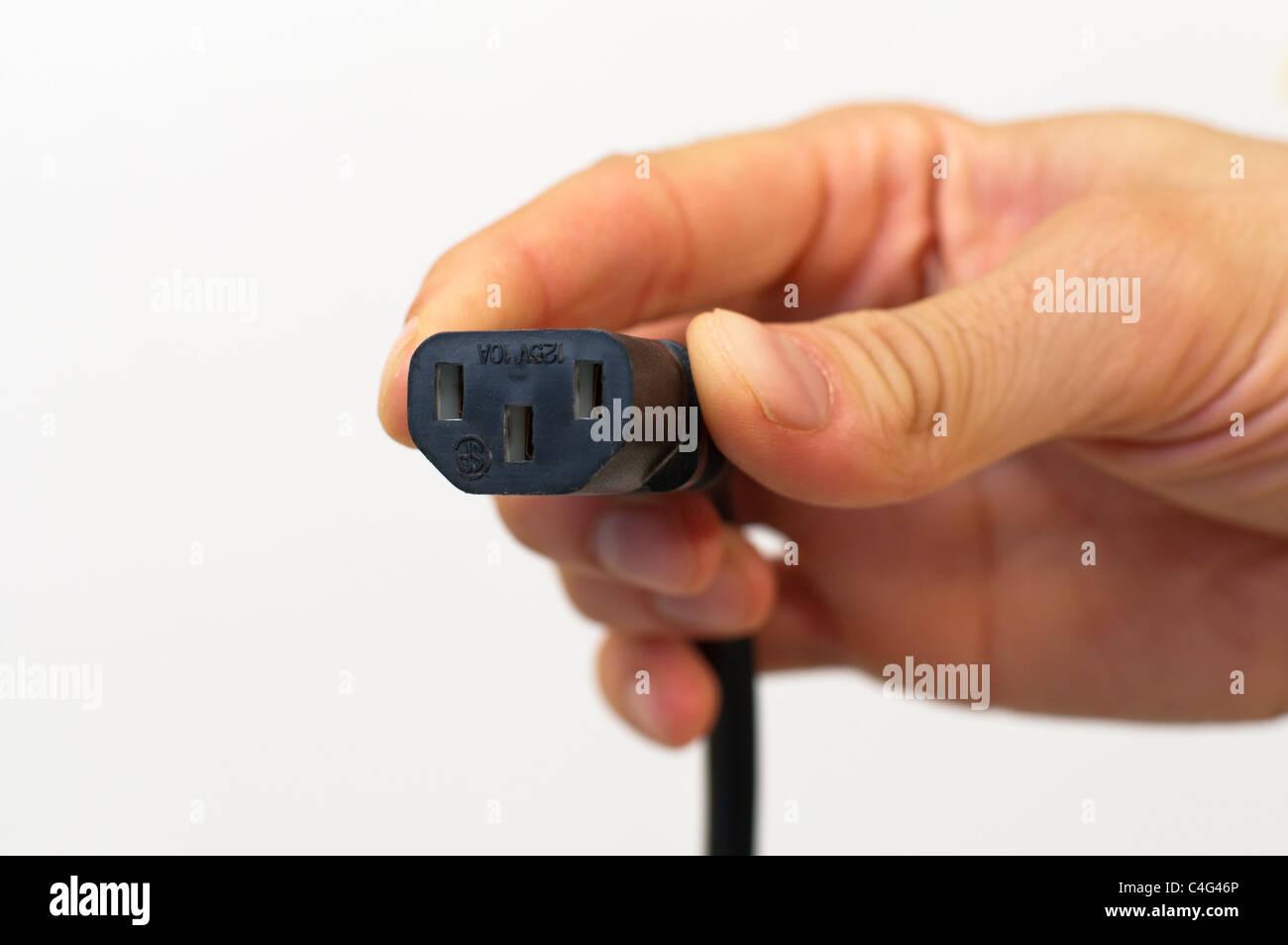 Hand, die einen elektrische Netzkabel Stockbild