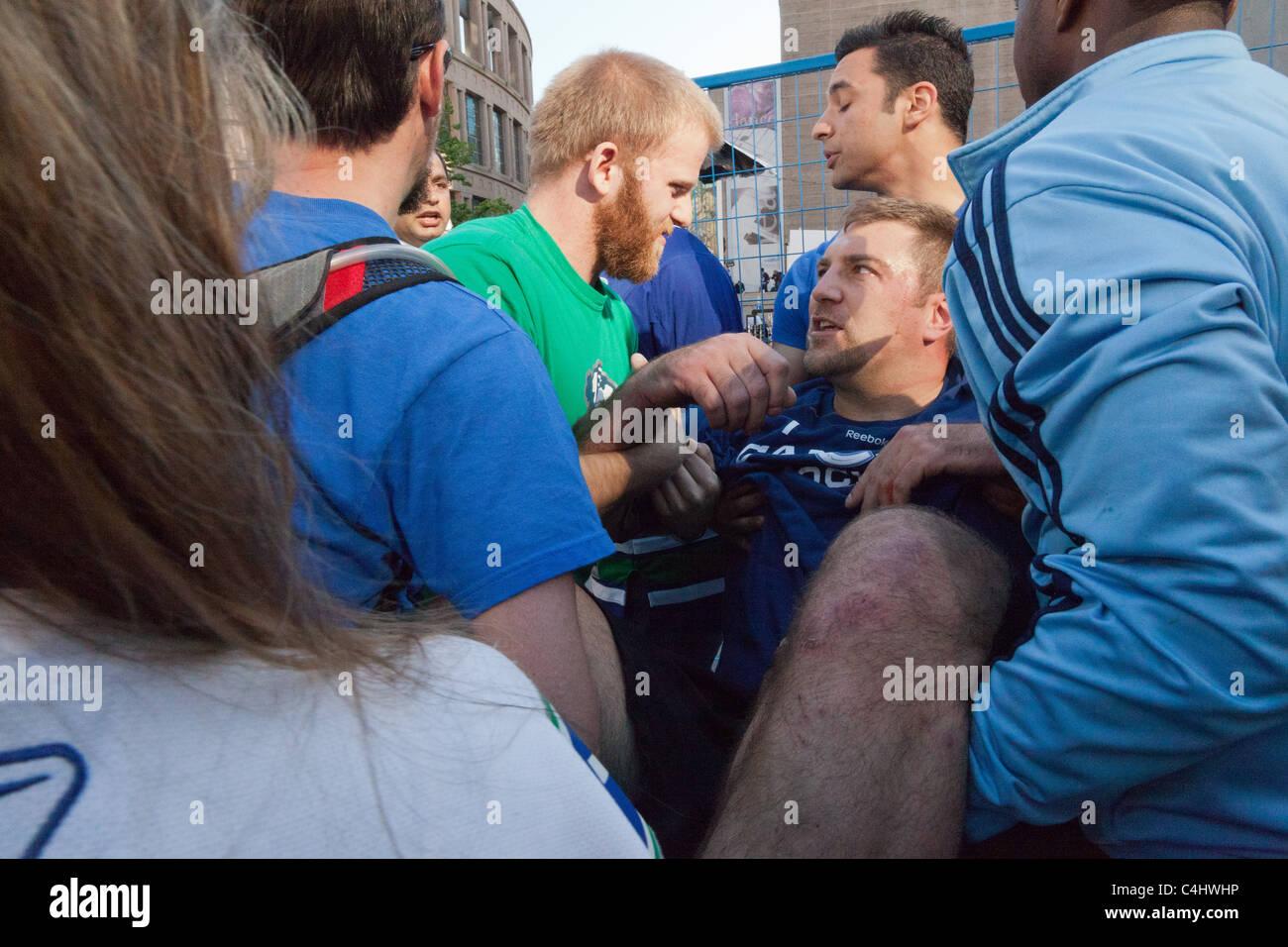 300 Pfund Mann bekommt von der Masse mit einem verdrehten Knöchel befreit, in Spiel 7 des Stanley Cups in der Innenstadt Stockfoto