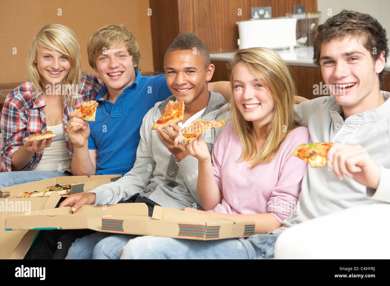 gruppe von jugendlichen freunde sitzen auf dem sofa zu hause essen pizza stockfoto bild. Black Bedroom Furniture Sets. Home Design Ideas
