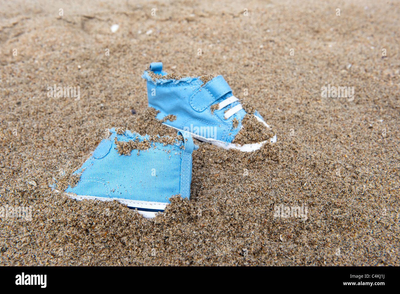 Ein paar Tennisschuhe Baby verloren an einem Sandstrand. Stockbild