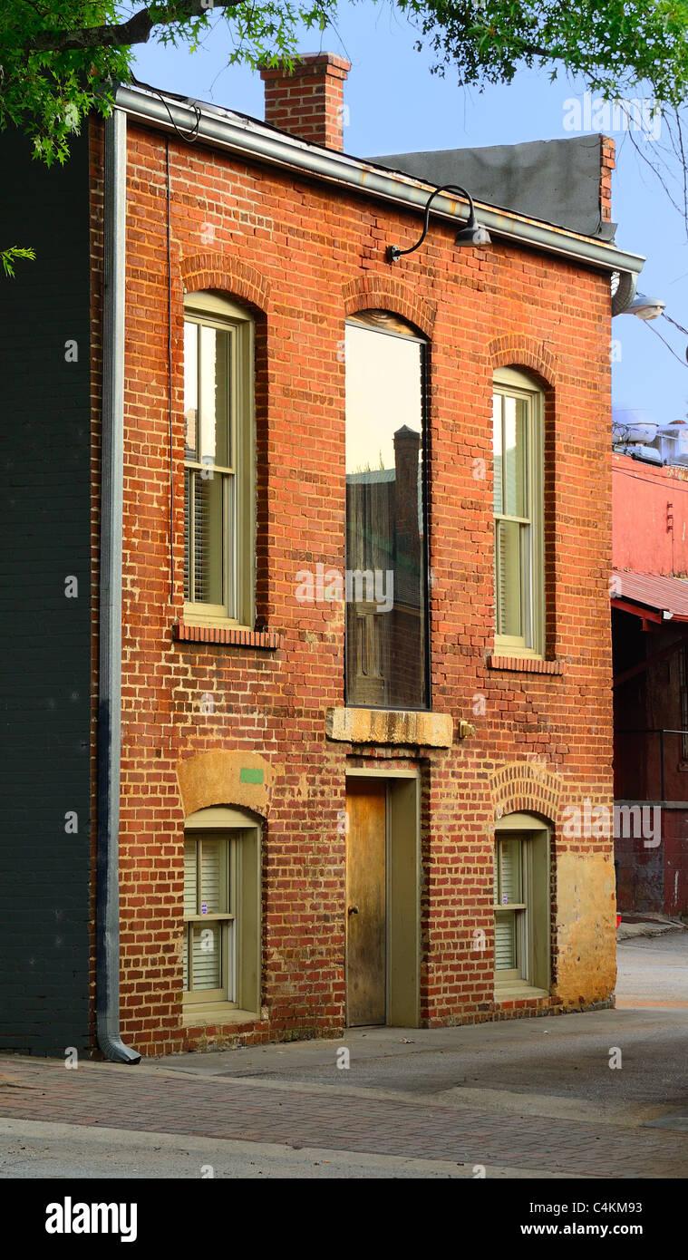 Fassade des heruntergekommenen Backsteingebäude Stockbild