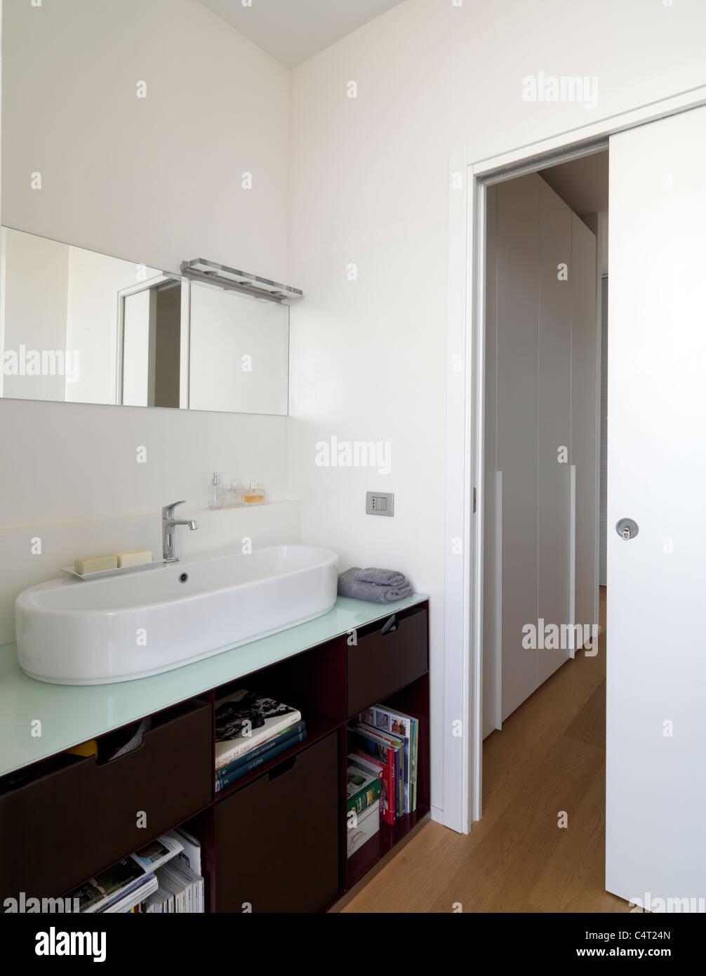modernes Badezimmer mit Holzboden und weiße Waschbecken, Schiebetür ...