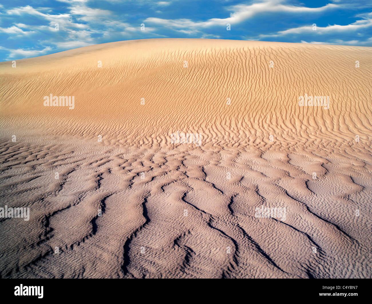 Wind kräuselt sich in Sanddünen. Death Valley Nationalpark, Kalifornien. Himmel wurde hinzugefügt Stockbild