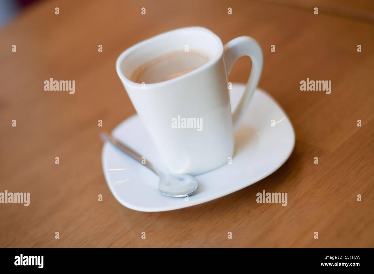 Eine frische Tasse Kaffee mit einem Teelöffel aus einem unabhängigen Cafe. Stockbild