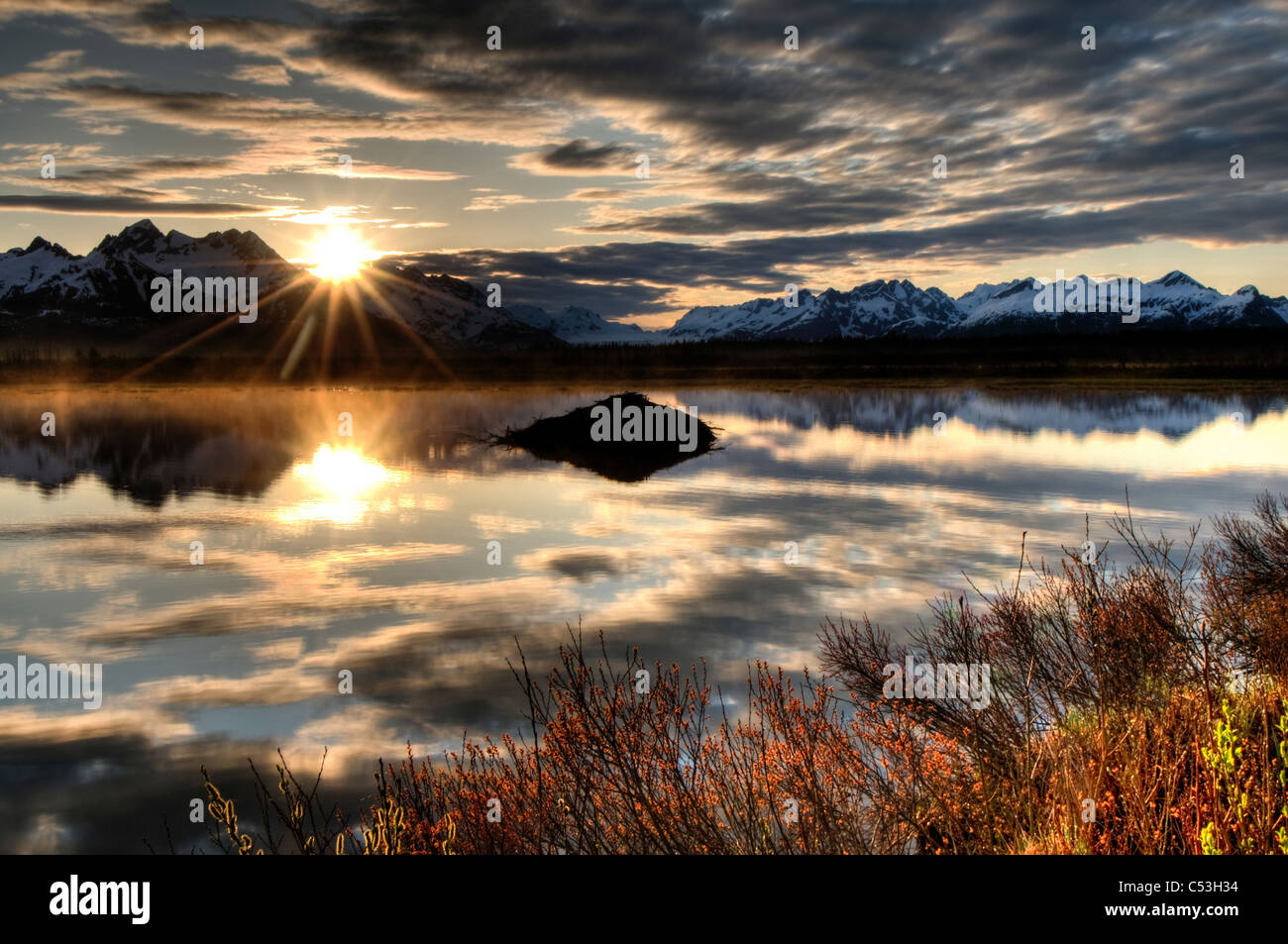 Sonnenaufgang über den Chugach Mountains mit einem Teich und Beaver Lodge im Vordergrund, Chugach National Stockbild