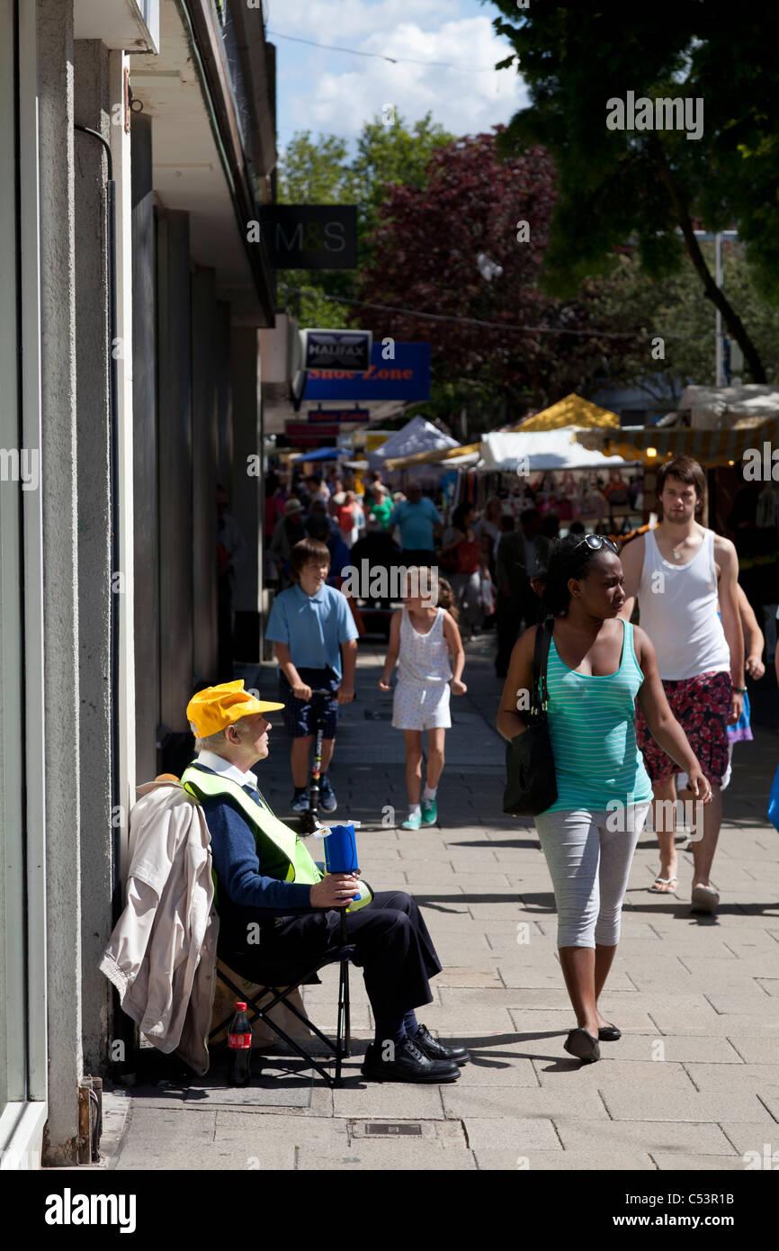 Liebe Sammler auf Stadtstraße sitzend, mit Menschen zu Fuß durch Stockbild