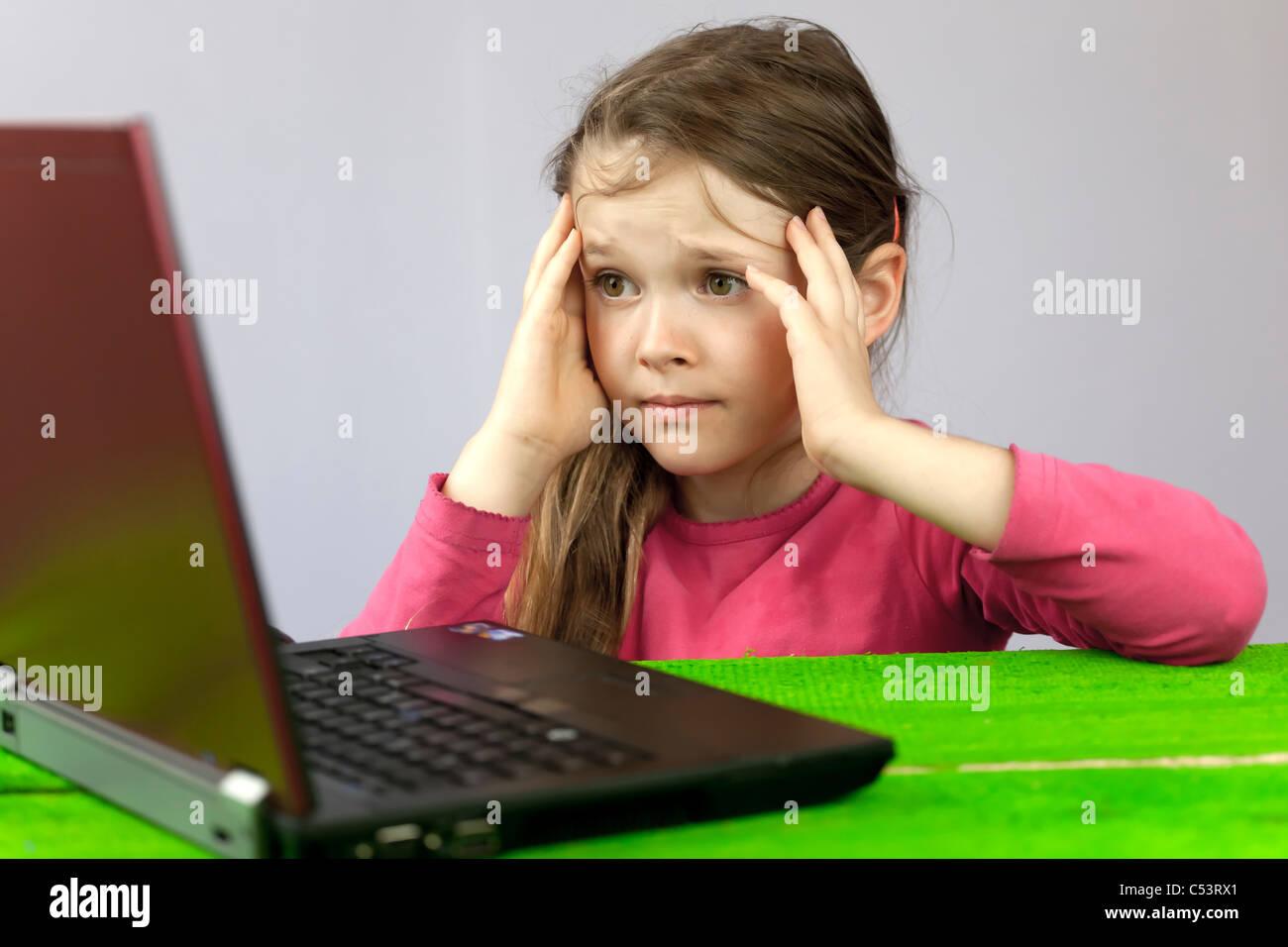 ein Mädchen auf dem Laptop, der Schwierigkeiten bei den Hausaufgaben hat Stockbild