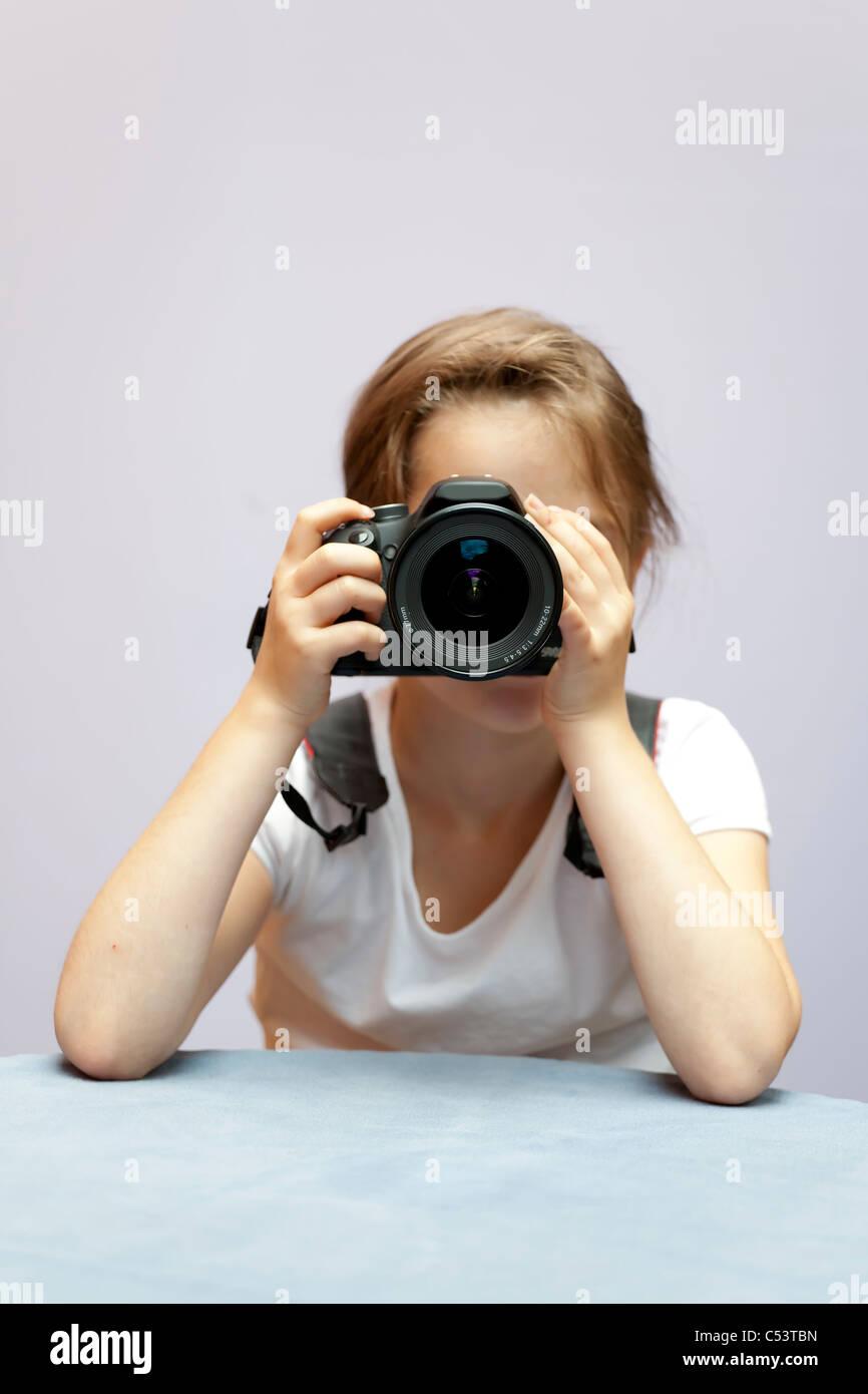sieben Jahre altes Mädchen, das eine SLR verwendet Stockbild