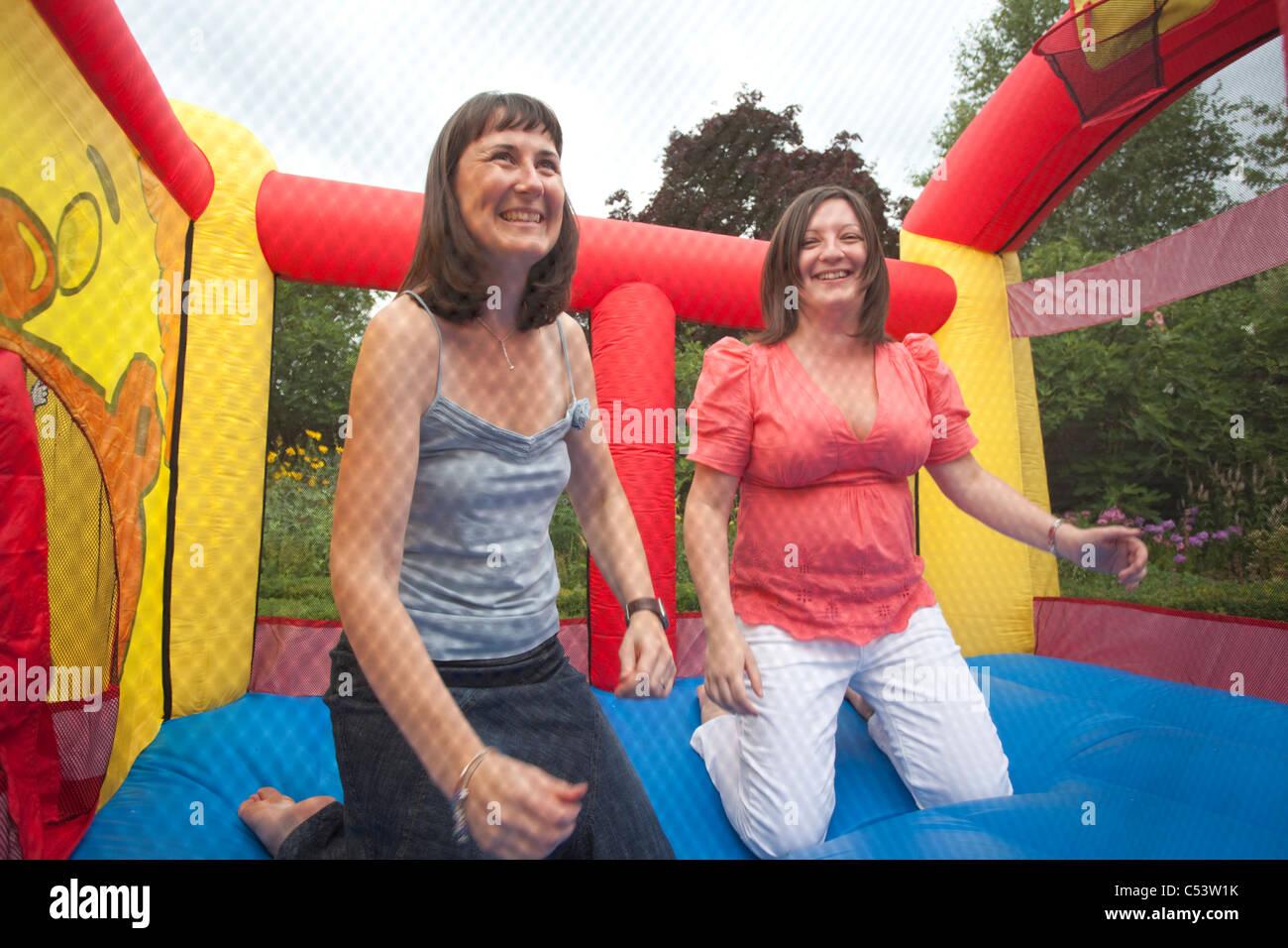 zwei adulte Weibchen auf der Hüpfburg spielen Stockbild