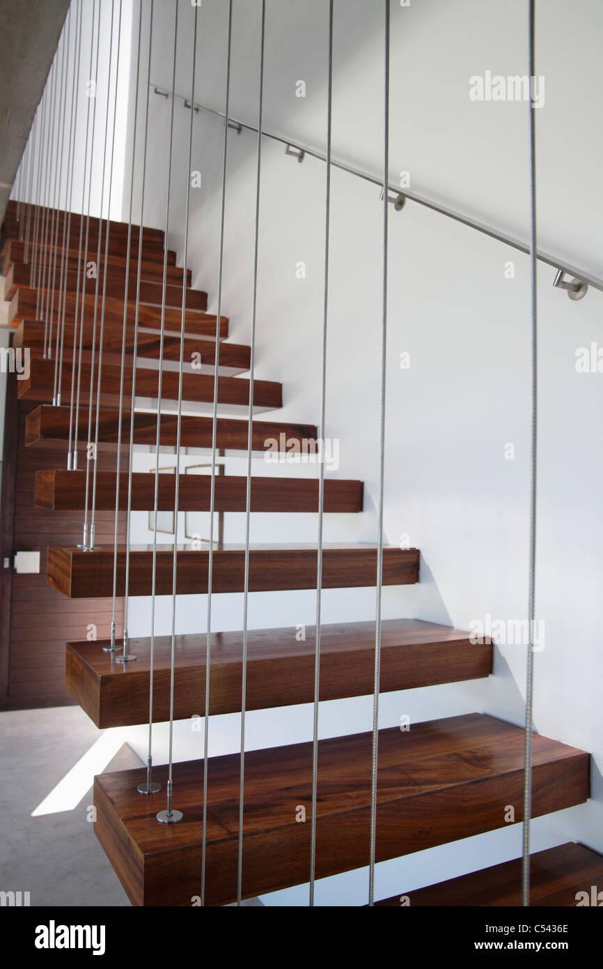 Holztreppe mit weißen Wänden und Metallgeländer Stockbild