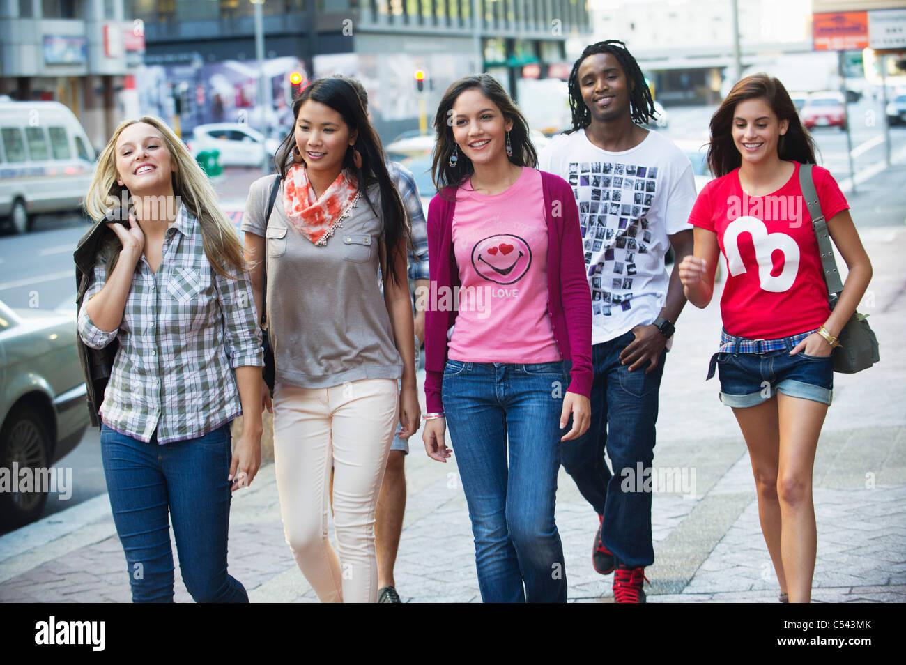 Freunde, die zu Fuß auf dem Bürgersteig gegen Autos Stockbild