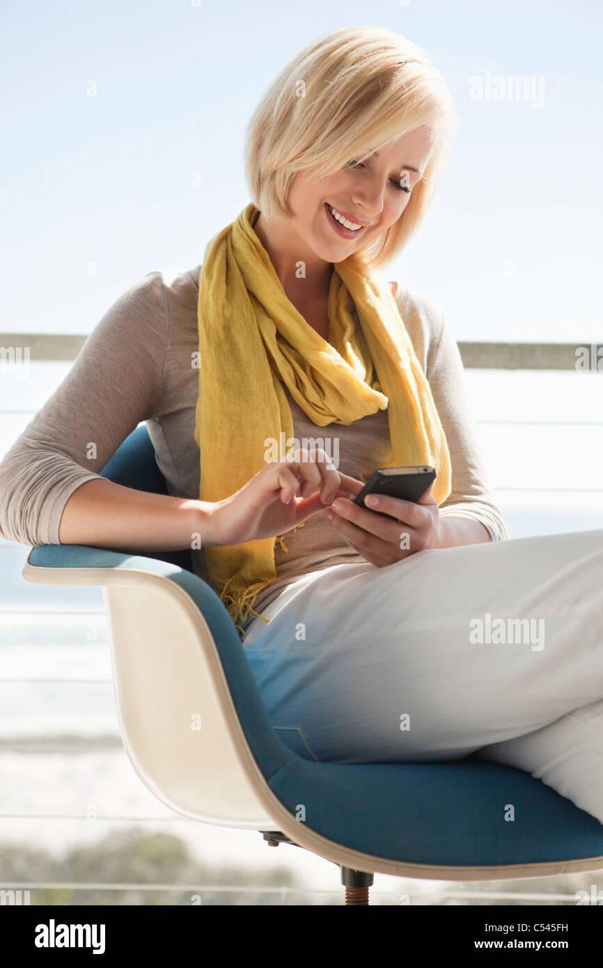 Frau von SMS-Nachrichten auf dem Handy Stockbild