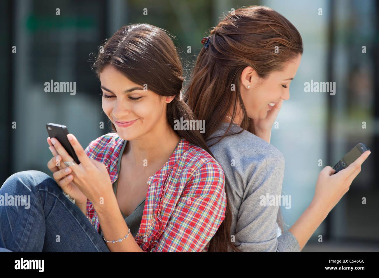 Zwei junge Frauen sitzen zurück zu Rückseite und Text-messaging Stockbild