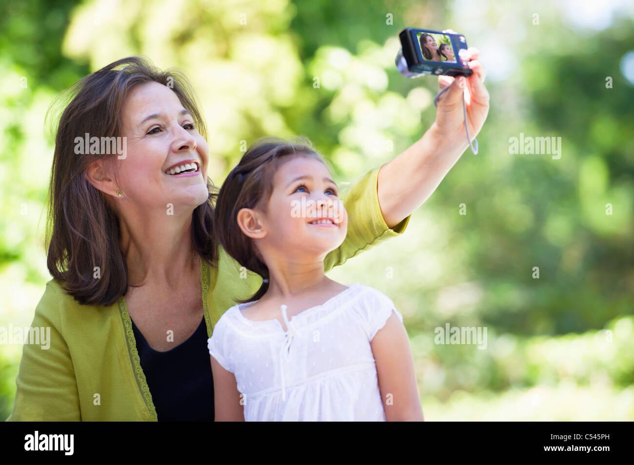 Frau und ihre Enkelin, die Fotos von sich selbst Stockbild