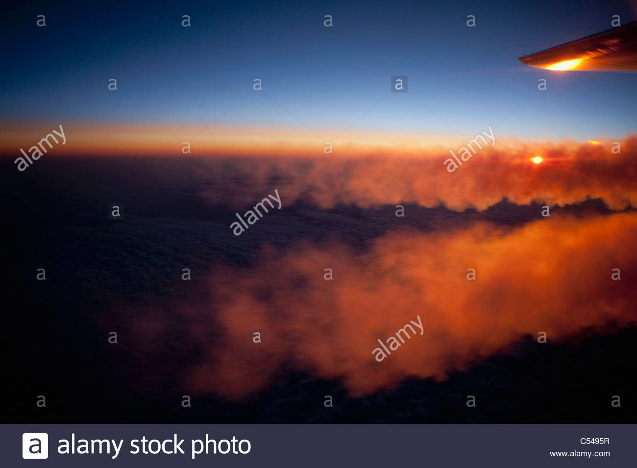 Die Niederlande, Amsterdam, Antenne, Sonnenaufgang über den Wolken, vom Flugzeug. Kondensstreifen oder Kondensstreifen. Stockbild
