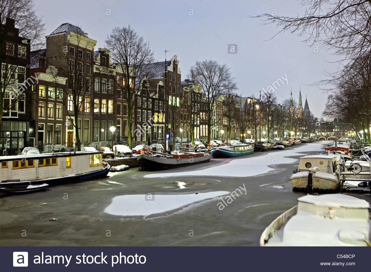 Niederlande, Amsterdam, Häuser 17. Jahrhundert am Kanal namens Keizersgracht. Winter, Schnee, Hausboote, Dämmerung. Stockbild