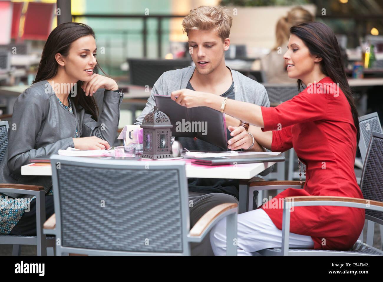 Junger Mann mit zwei jungen Frauen Blick auf die Speisekarte in einem restaurant Stockfoto