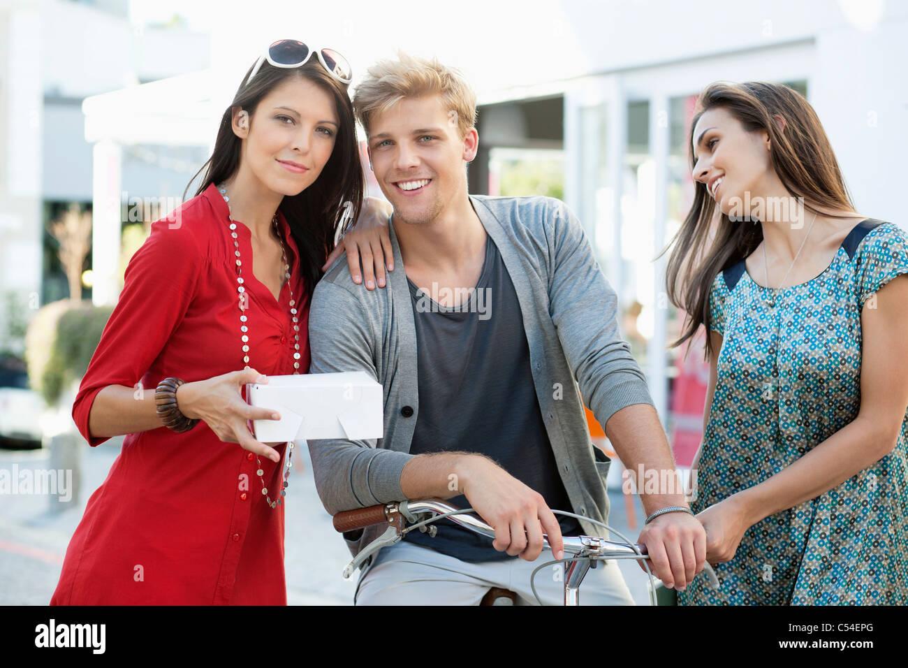 Porträt eines jungen Mannes mit zwei Frauen, Radfahren Stockfoto