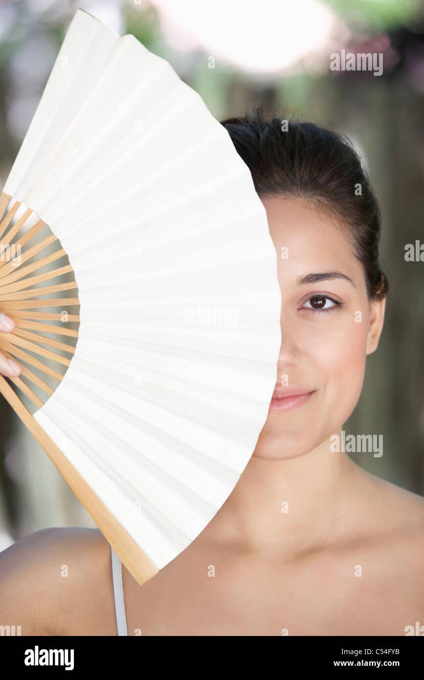 Schöne junge Frau, die ein chinesischer Fan vor ihr Gesicht halten Stockbild