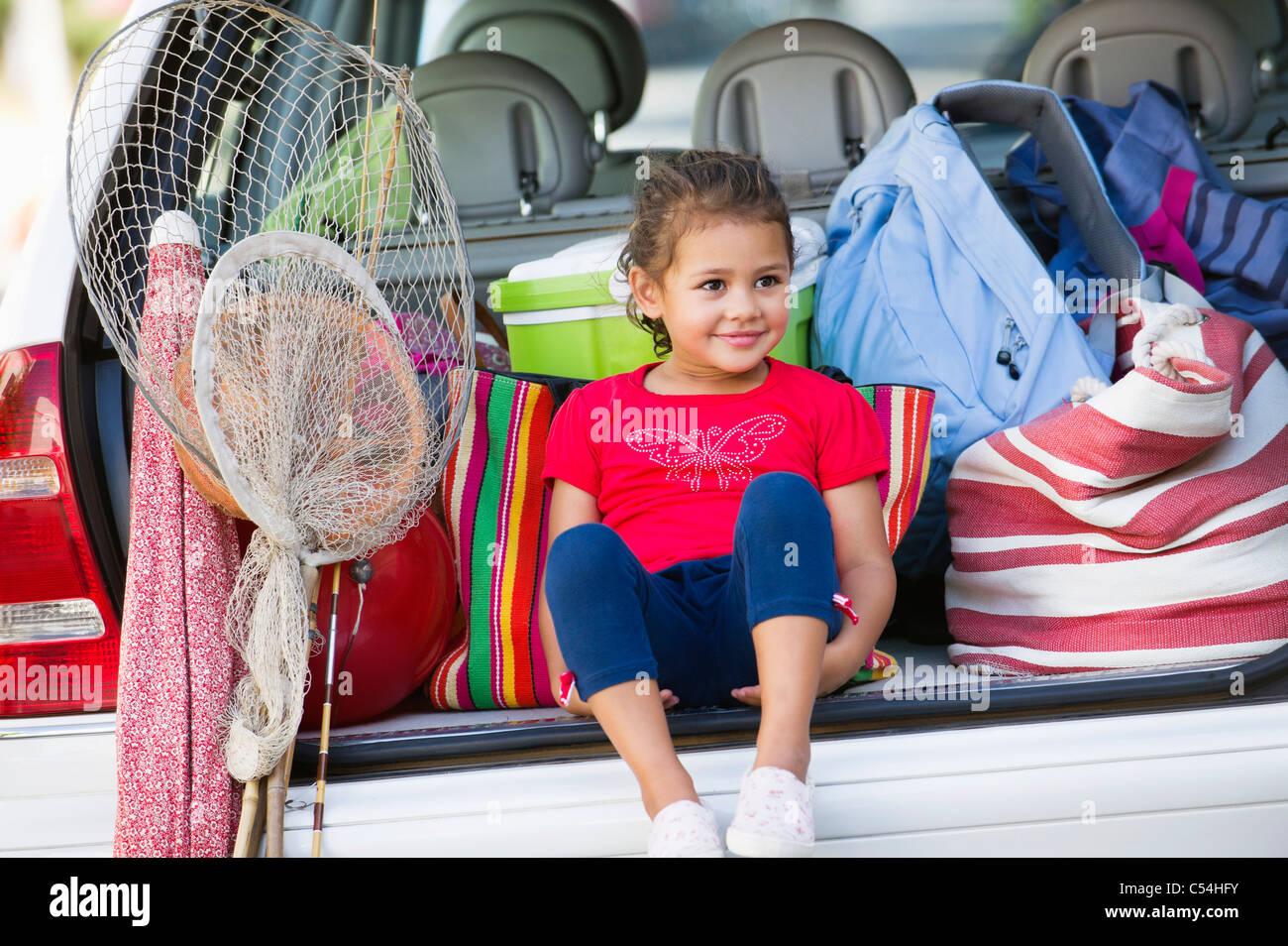 Niedliche kleine Mädchen sitzen im Kofferraum eines Autos Stockfoto