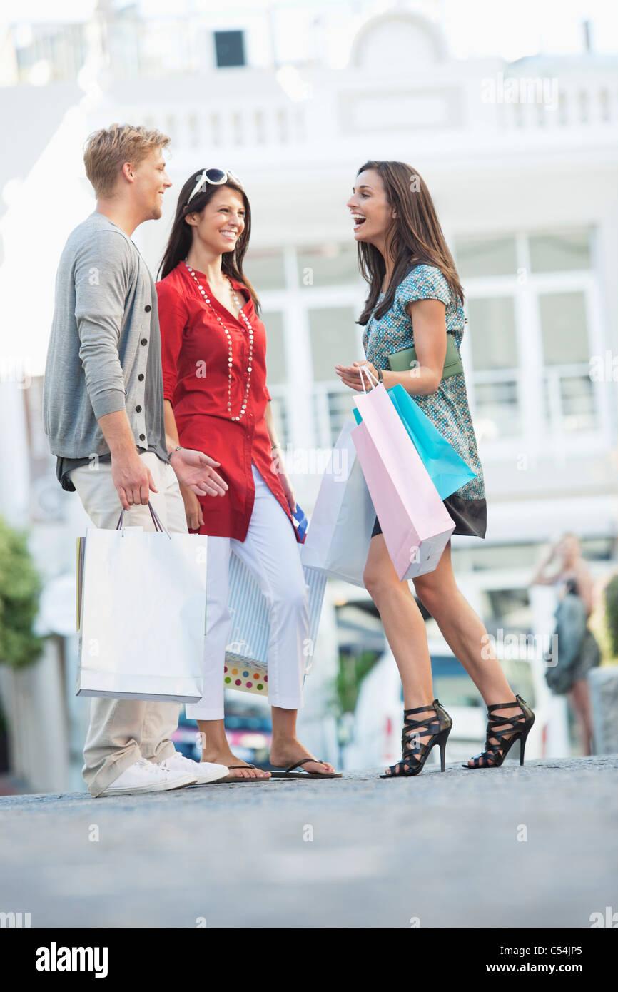 Junger Mann mit zwei Frauen halten Einkaufstaschen auf einer Straße Stockfoto