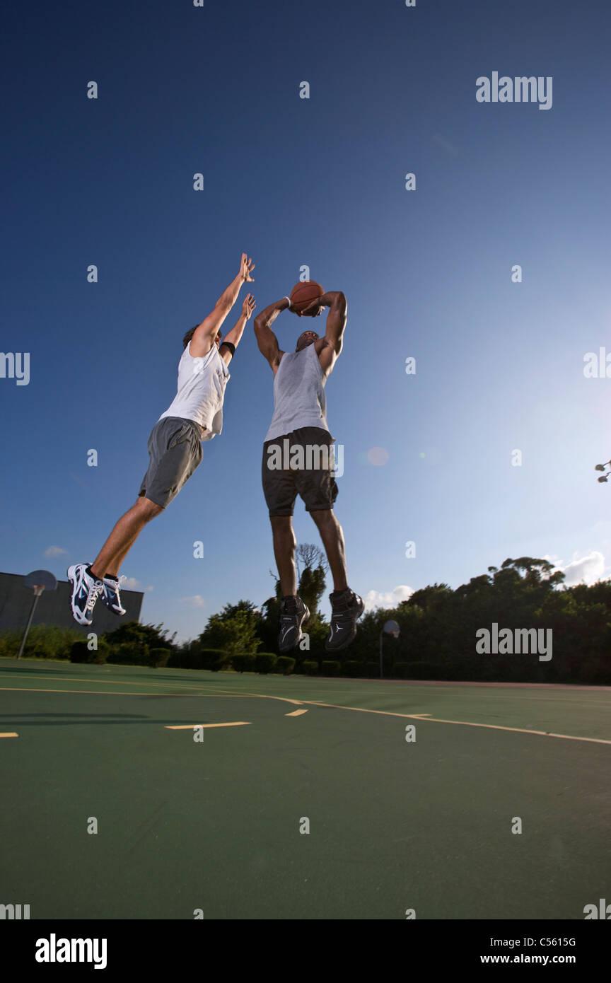 Sprungwurf im freien zwei auf zwei Basketball-Spiel, verteidigt Stockbild