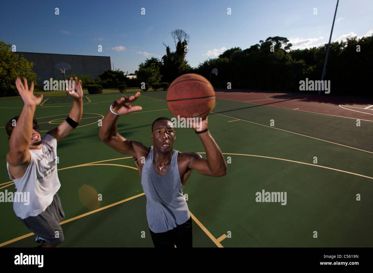 Männer spielen im freien Basketballspiel Stockbild