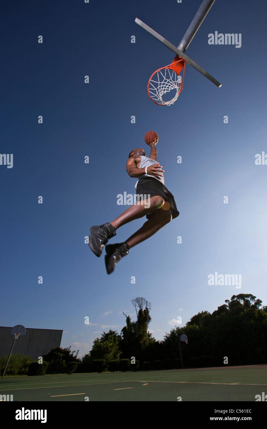 männliche macht Dunk, Layup auf Outdoor-Basketball-Ziel Stockbild