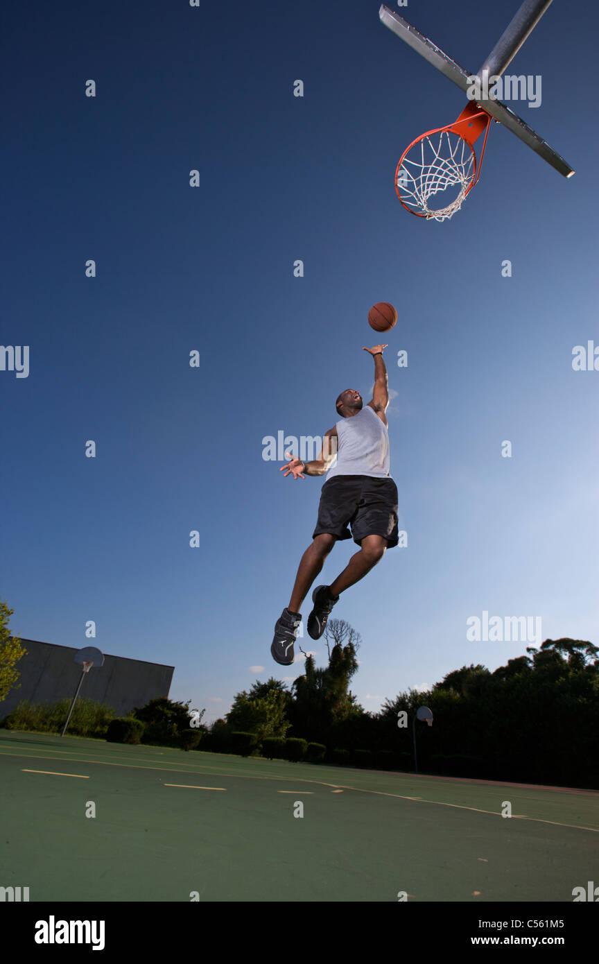 Männlich, scoring Layup auf Outdoor-Basketball-Ziel Stockbild