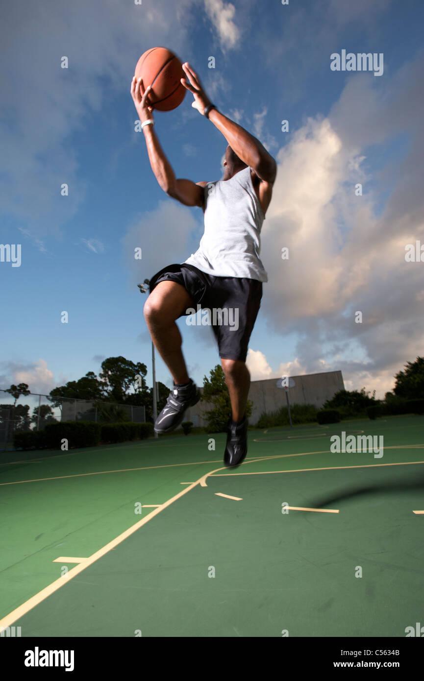 Männchen machen vertikale springen bei Outdoor-Basketball-Spiel Stockbild