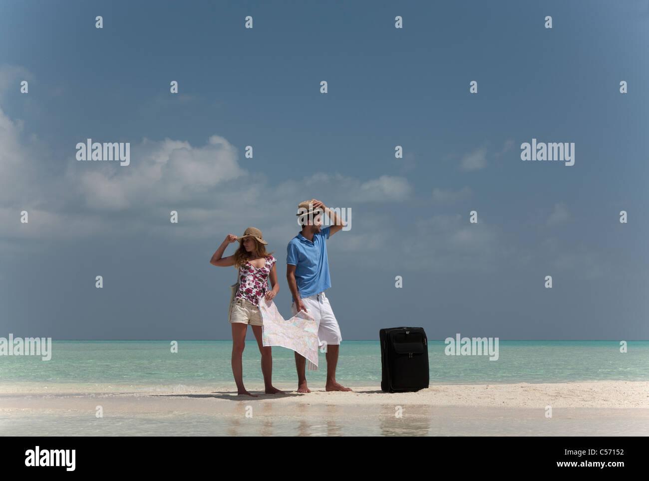 Verlorene paar Holding Karte am Strand Stockbild