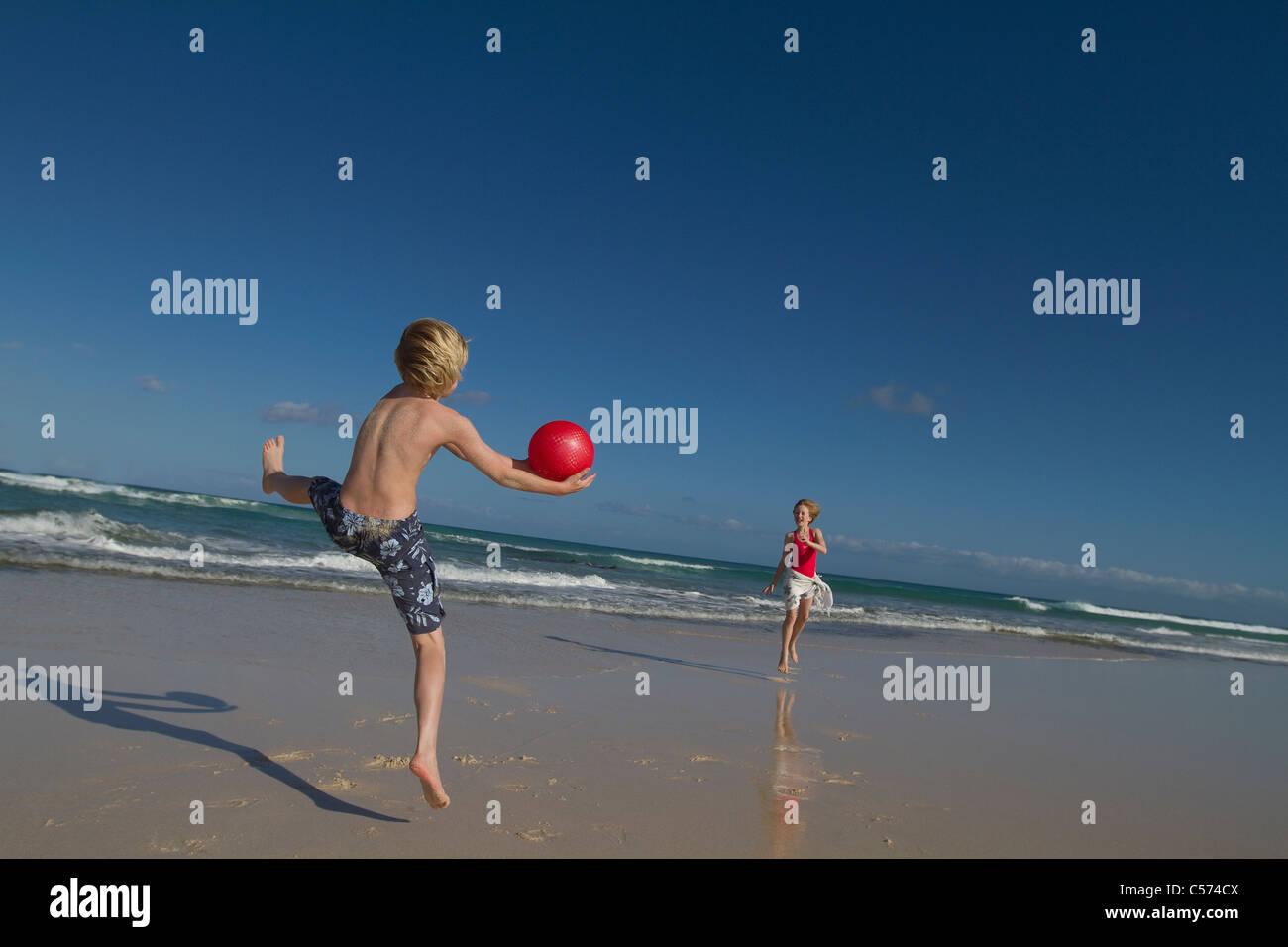 Kinder spielen mit roten Ball am Strand Stockfoto