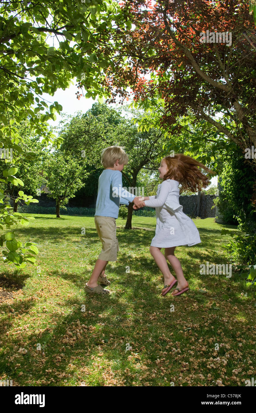 Boy girl holding hands spinning stockfotos boy girl - Kinder im garten ...