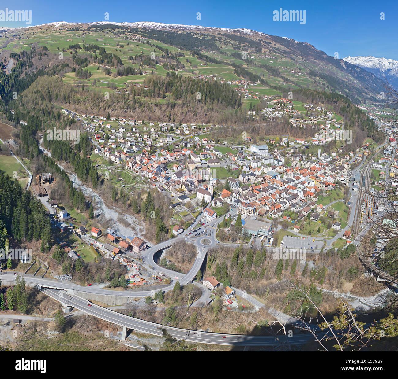 Frühling Alpenpanorama der kleine Bergstadt im Tal in die große Straße und Schiene Infrastruktur, Stockbild