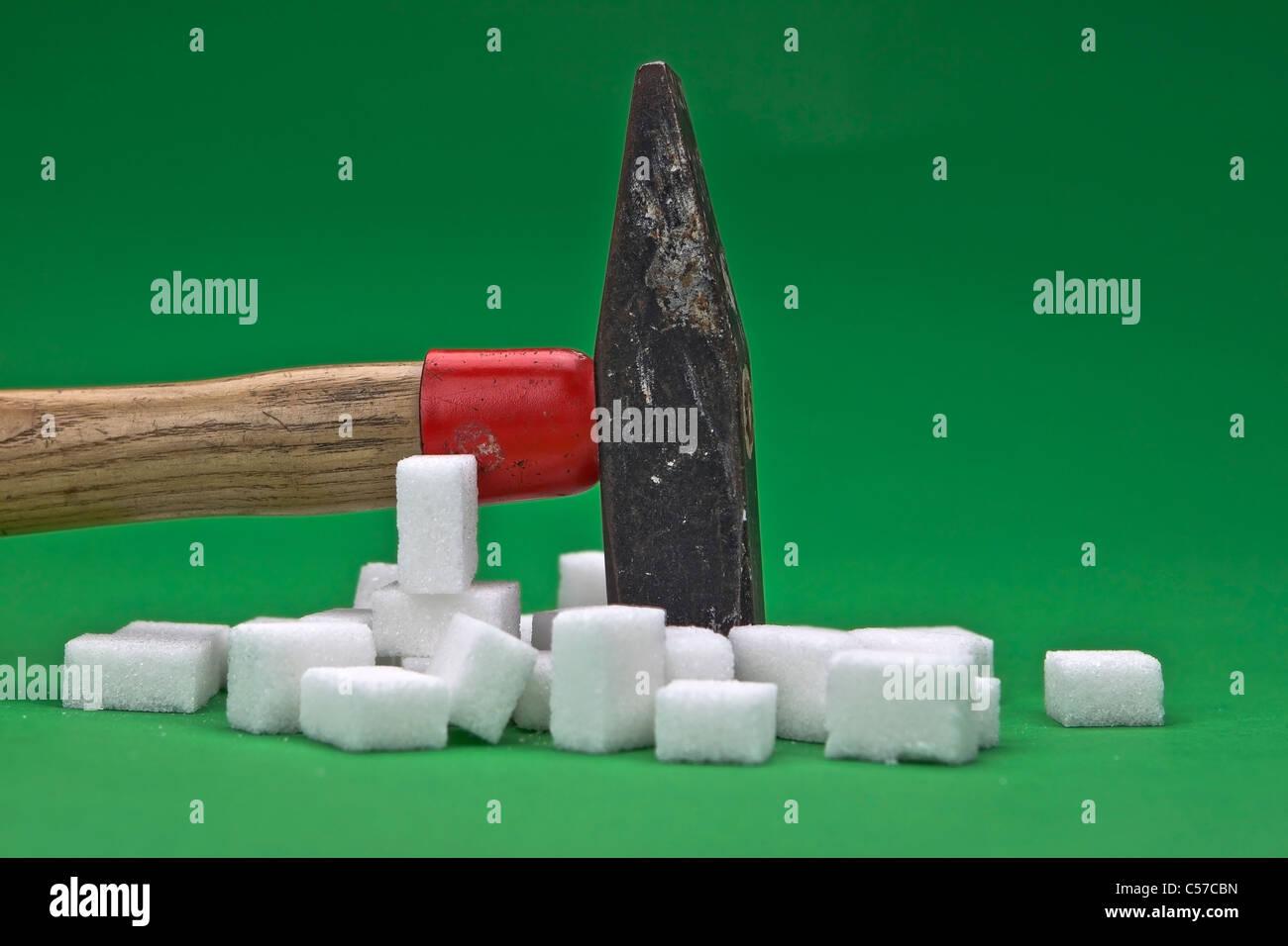 einen Hammer der störenden Würfelzucker für eine gesündere Ernährung in der Zukunft liegt Stockbild
