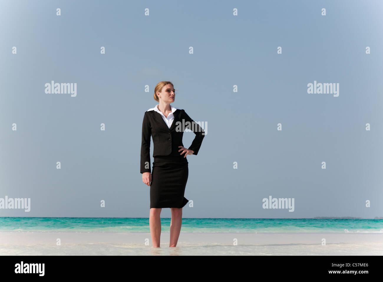 Geschäftsfrau, stehend am tropischen Strand Stockbild