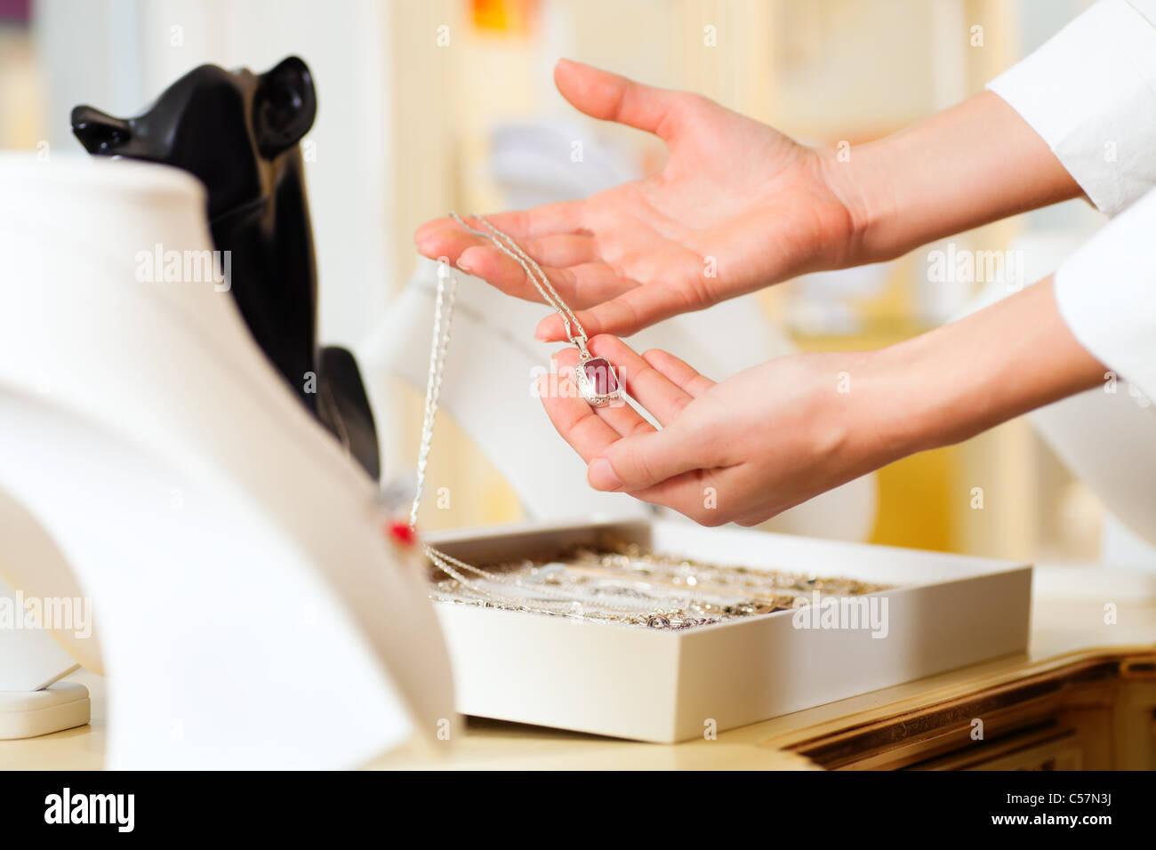 weibliche juwelier oder designer prasentieren schmuck in ihrem laden