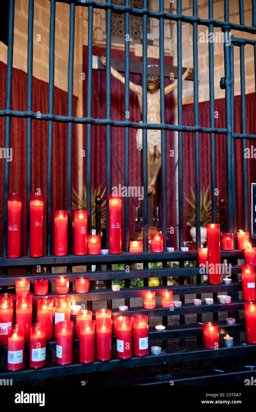 Blick auf die Kreuzigung Christi in der roten Gebet Kerzen an dem Heiligkreuz und Kathedrale Saint Eulalia von Barcelona, Stockbild