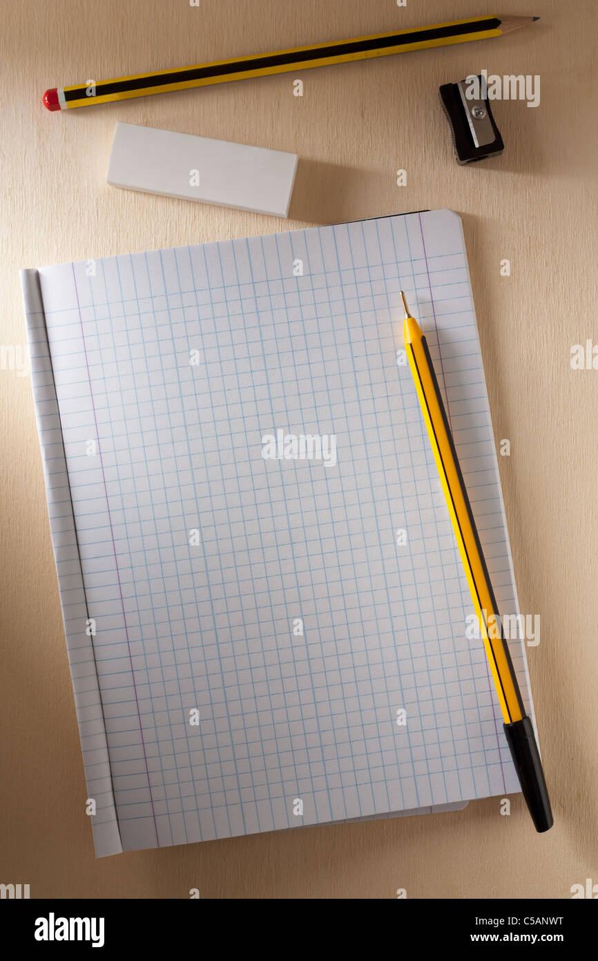 Leere Schulheft mit Kugelschreiber, Bleistift, Kautschuk und Bleistiftspitzer Stockbild