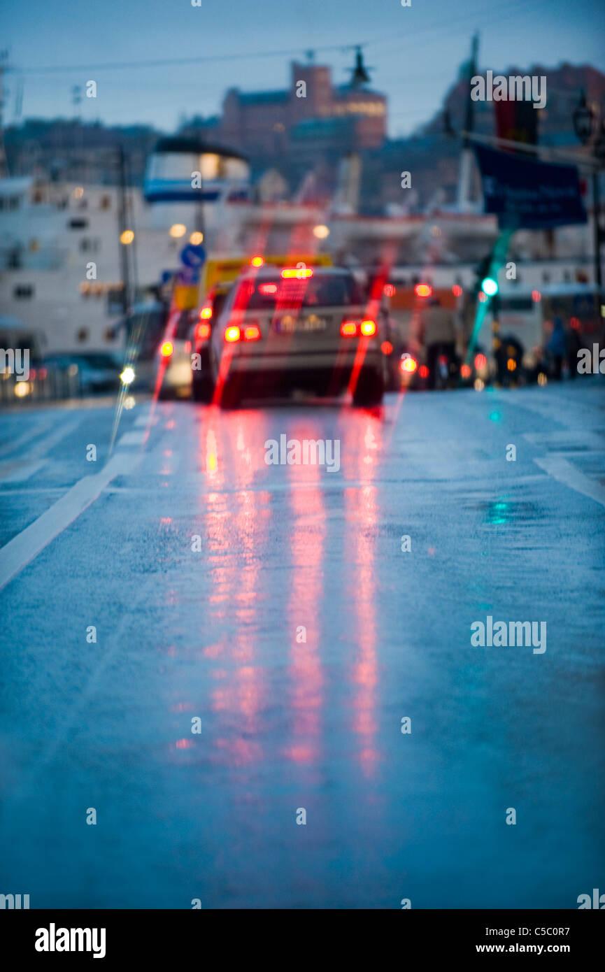 Distanz-Schuss Bremslichter im Regen mit leeren Asphaltstraße im Vordergrund Stockfoto