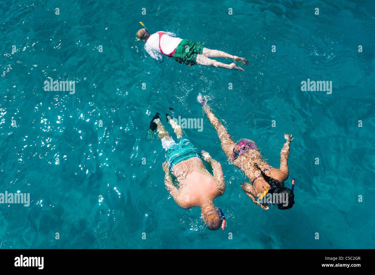 Draufsicht von drei Jugendlichen im türkisfarbenen Wasser Schnorcheln Stockfoto