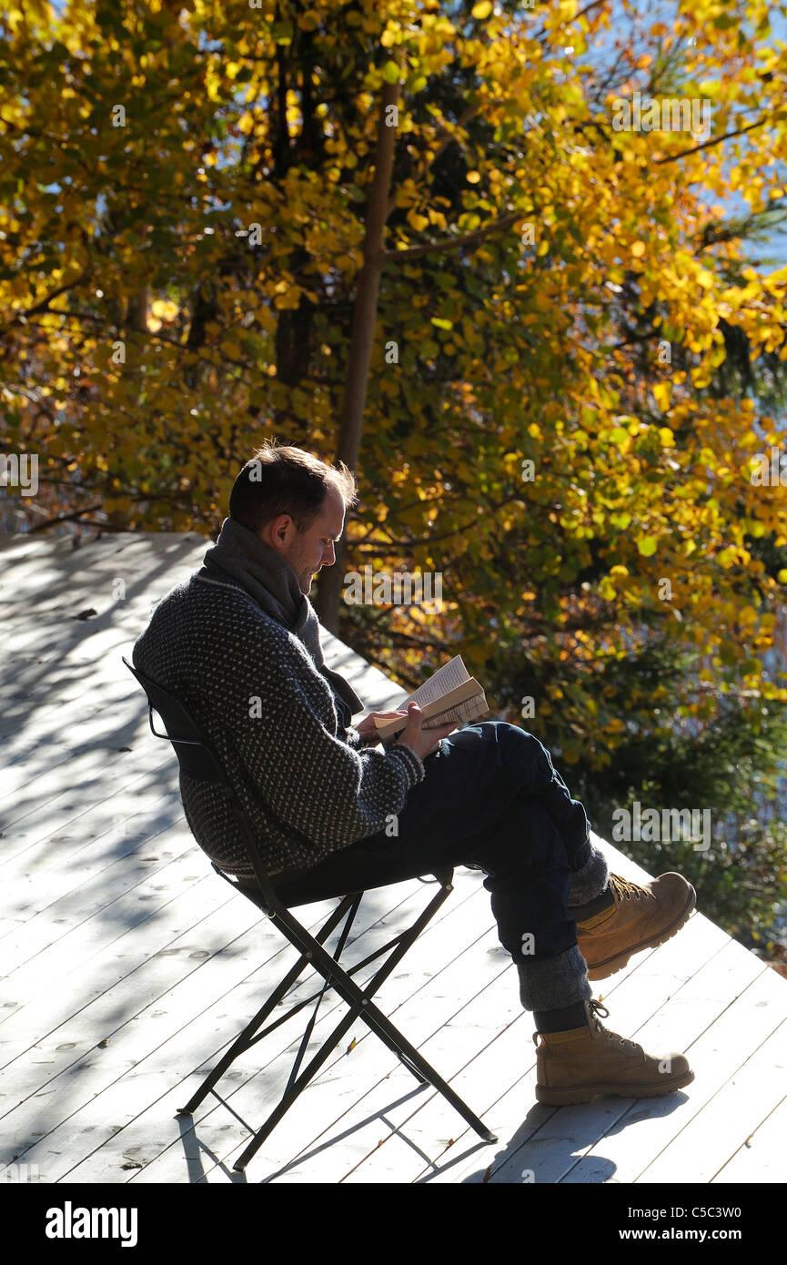 Seitenansicht eines Mannes, ein Buch mit herbstlichen Bäume im Hintergrund Stockbild