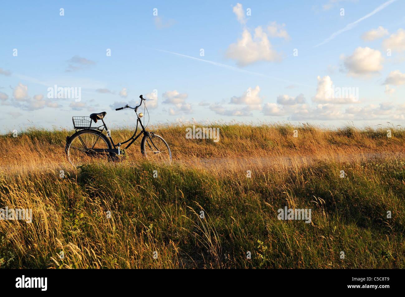 Fahrrad auf einem küstennahen Holzsteg gegen einen schönen blauen Himmel, Nordseeinseln Deutschlands, Stockbild