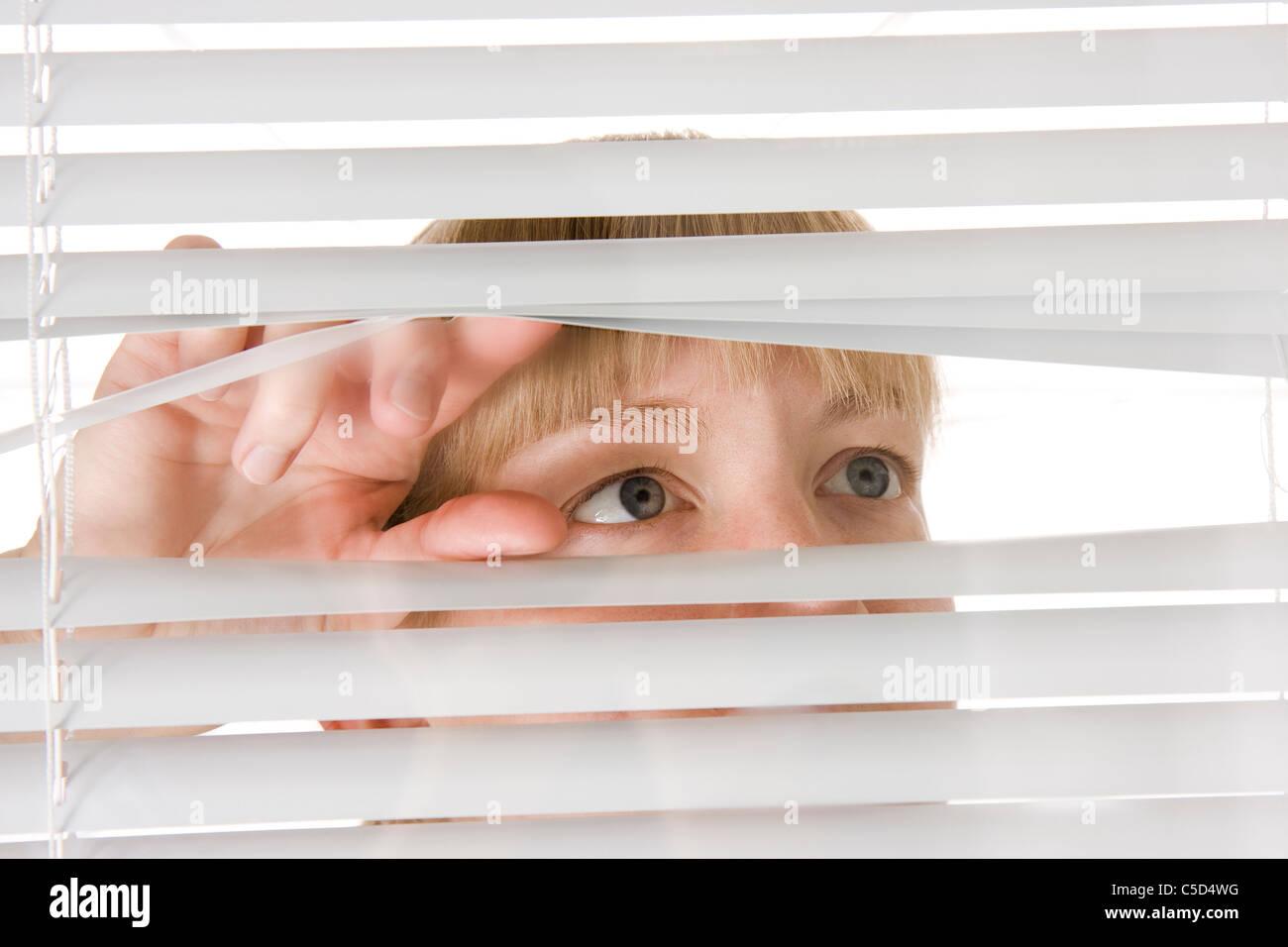 Nahaufnahme einer Frau heimlich Blick durch Jalousien Stockbild