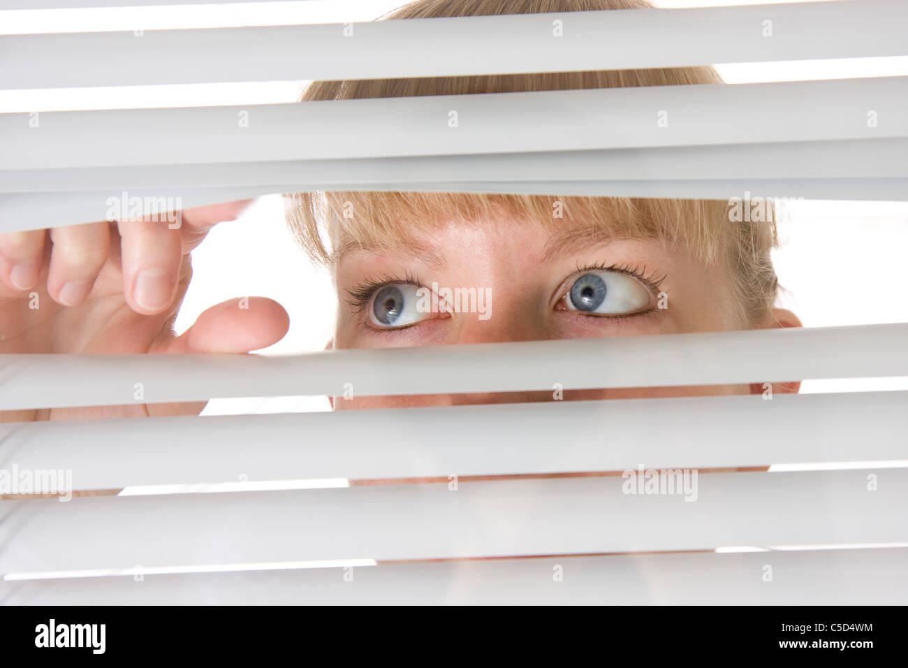 Nahaufnahme von einer blauen Augen Frau heimlich durch Jalousien Stockbild